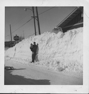 Blizzard of 1966. Stanly Diele and son, Jan, standing by a snowbank in front of Pinke Lumber Company. Sayler's Standard is in the background.